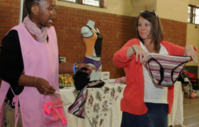 A girl demonstrates how to use the new washable sanitary towels.