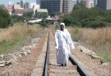 An Apostolic woman walks along train tracks on her way back from a mountain prayer session.