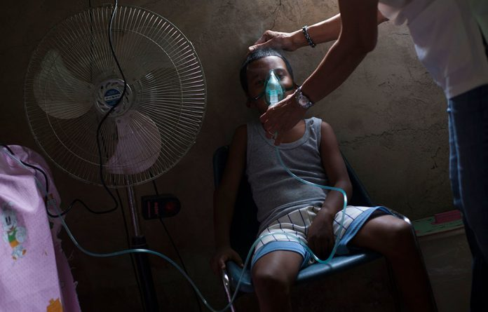 A nine-year-old boy breathes from a nebuliser as he seeks treatment for his asthma.