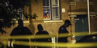 A woman watches from her window as police look for evidence after 20-year-old Carlos Barron was shot and killed in Chicago. The city is still very racially segregated and has high rates of violence.