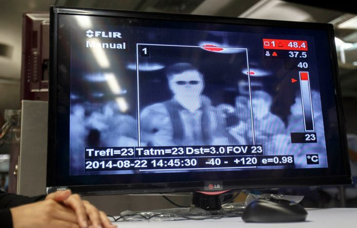 Feeling the heat: Passengers are screened with thermal imaging cameras for illness at Bangkok's ?Suvarnabhumi Airport in a bid to avert the spread of Ebola.