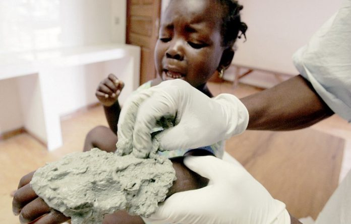 A nurse treats a young patient's buruli ulcer with a clay poultice.