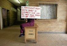 A health worker hides their face while holding a placard detailing shortcomings at Chris Hani Baragwanath Hospital in 2014. This year