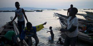 Boys prepare fishing boats for night fishing in Lake Tanganyika at sunset.