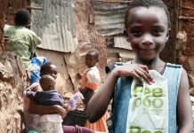 A girl in Kibera holds up the Peepoo