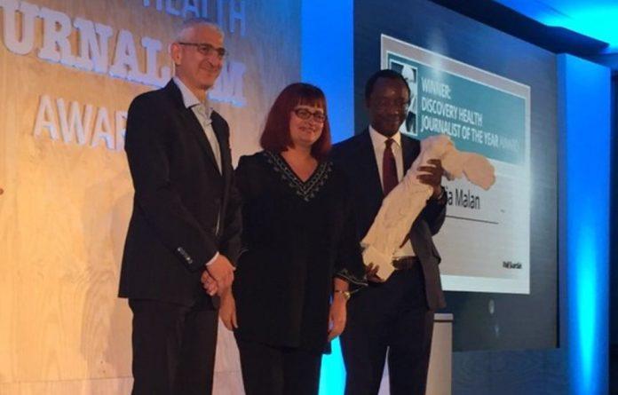 Mia Malan accepts the Discovery Health Journalist of the Year award from CEO Jonathan Broomberg and Professor Tawana Kupe.