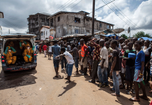 Volunteers arrive to pick up bodies of people who died of Ebola in the 2014-2015 outbreak.