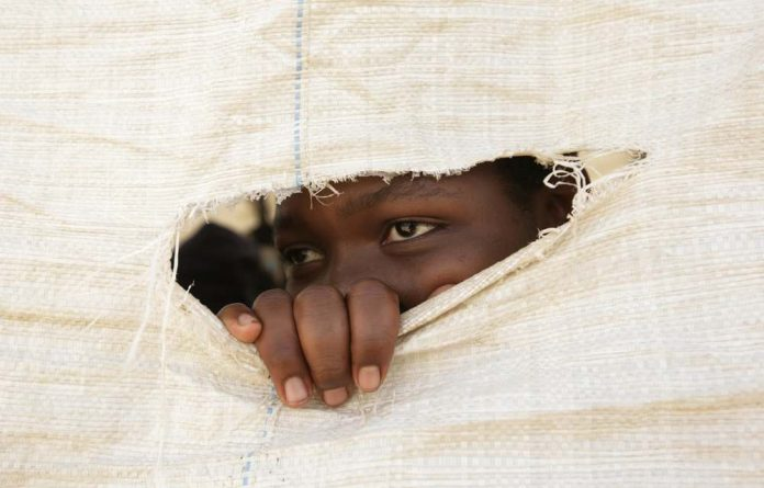 A Zimbabwean secondary school student peeps through a hole in a sack that forms the wall of a makeshift classroom.