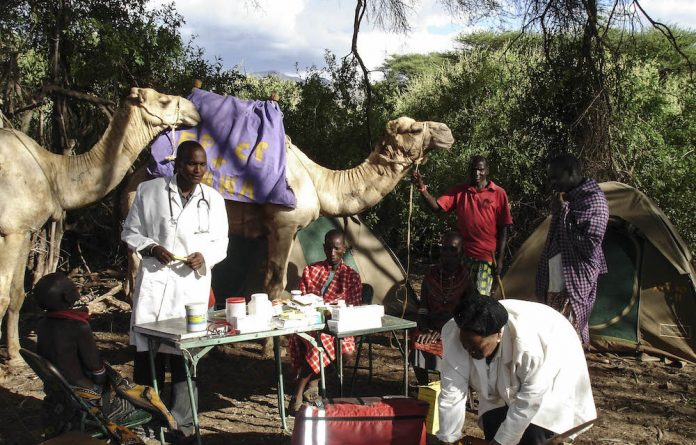Nurse Pauline dips into a medicines box. Pauline and her team travel hundreds of kilometres by camel to provide health services to Kenya's most remote villages
