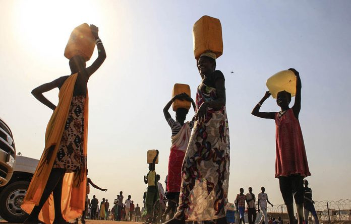 Displaced people carry water containers on their heads at Tomping camp