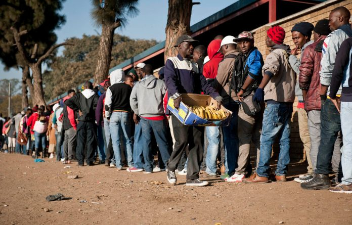 Asylum seekers wait to apply for permits at Home Affairs in Marabastad. The Help@Hand app helps refugees and asylum seekers to access services.
