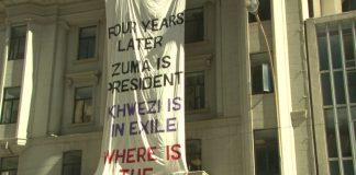 """Protestors from the One in Nine Campaign stage a demonstration. Constitutional Court judge Zak Yacoob said in 2014 that he 'believed the Zuma trial was not about finding the truth"""" but about story telling."""