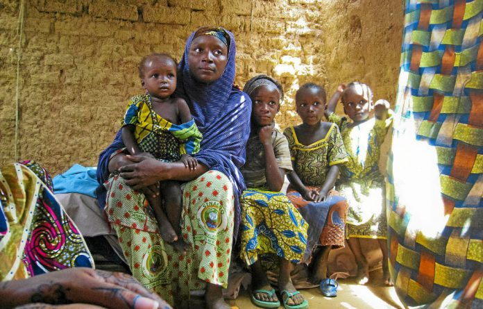 A woman and her children in a village in Niger. A child born in 1960 had an 18% chance of dying before his or her fifth birthday. Today