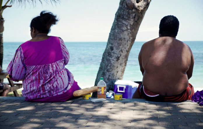 An obese couple sits on the beach. Overweight and obesity have been recognised as crucial health issues and have been included in the sustainable development goals.