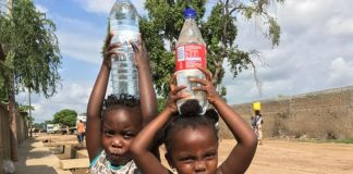 Girls carry bottled water in Maputo