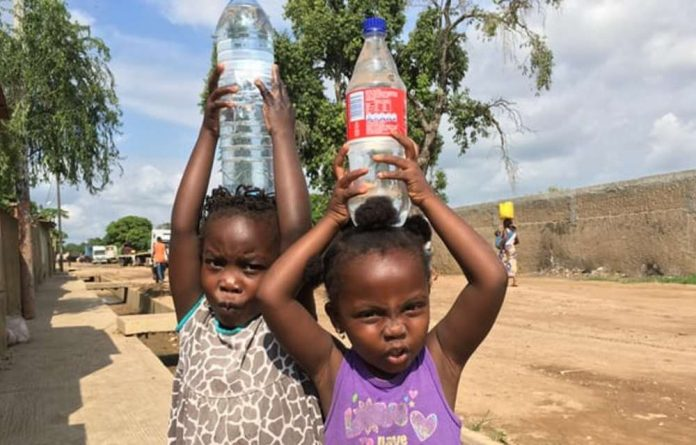 Girls carry bottled water in Maputo