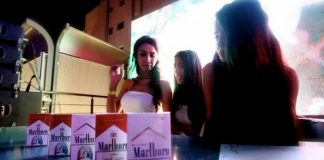 Young girls pose with boxes of Marlboro cigarettes.