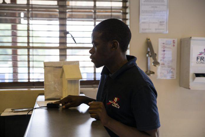 Man scans his fingerprint to receive medication.