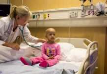 A doctor bends down to check young cancer patient's heartbeat.