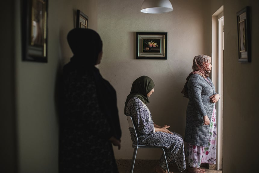 Women in hijab waiting and looking out of a door.
