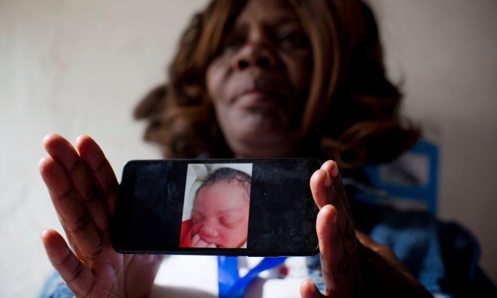 Midwife Pamela Dochieng holds up her phone to show a photo of a baby that was delivered and then abandoned at a clinic in Kibera. (Kate Holt, The Guardian)