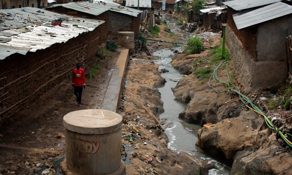 A man walks past a spot in Kibera where a dead baby was left. (Kate Holt, The Guardian)
