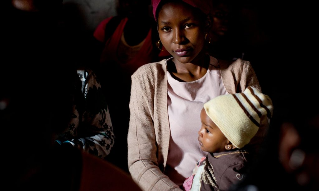 A young mother holds her baby at a community meeting in Kibera. (Kate Holt, The Guardian)