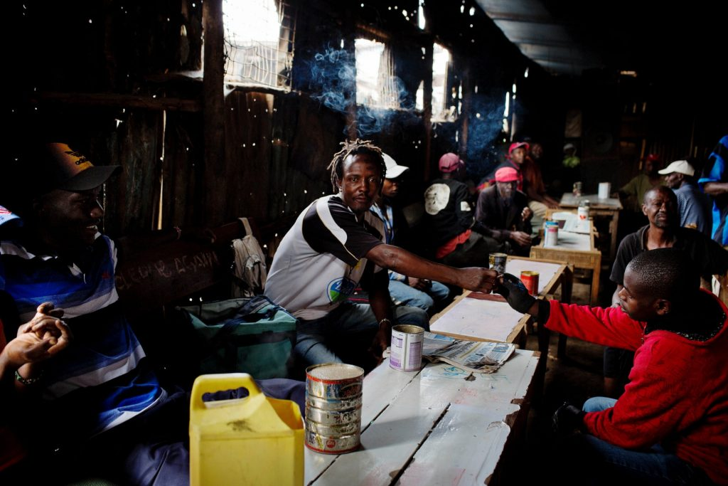 Men drink changaa — home-brewed alcohol — in a bar in Kibera. (Kate Holt, The Guardian)