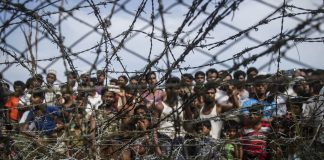 No man's land: People gather behind a barbed wire fence in a temporary settlement on the Myanmar border. When governments fail, aid organisations step in. But who should they report to? (Ye Aung Thu, AFP)