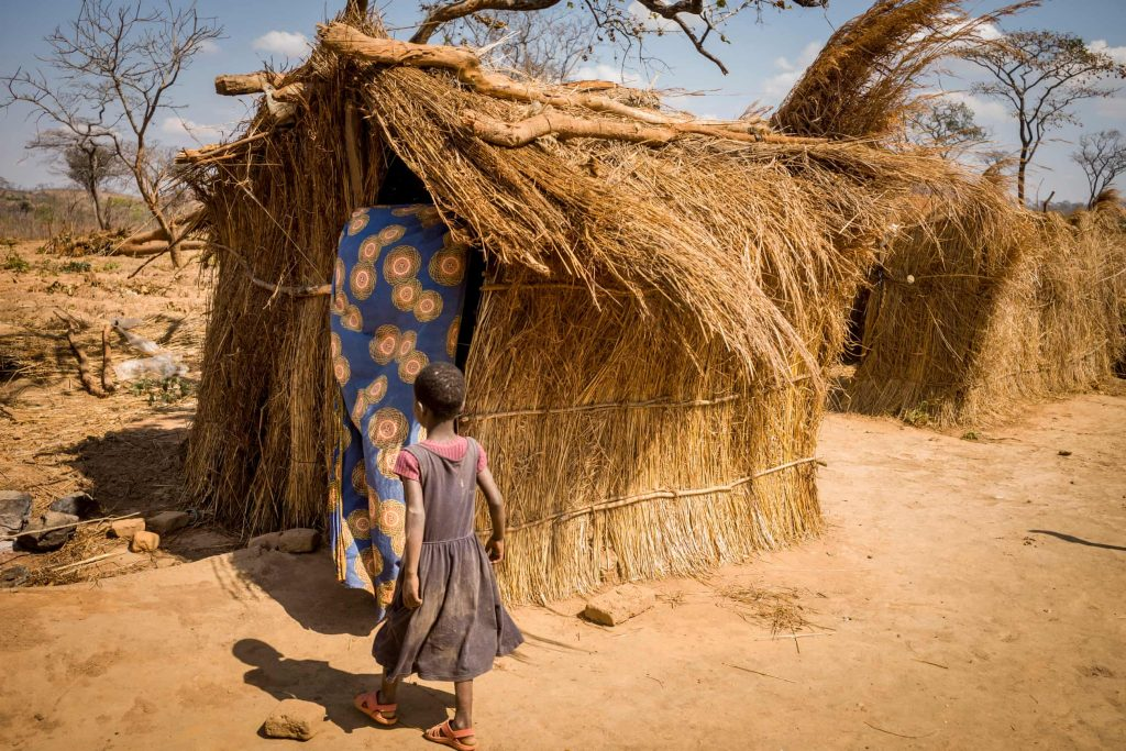 A girl beside her straw home, which offers little protection during the rains. (David Lee)