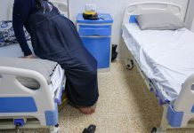 A pregnant woman sits on a hospital bed.